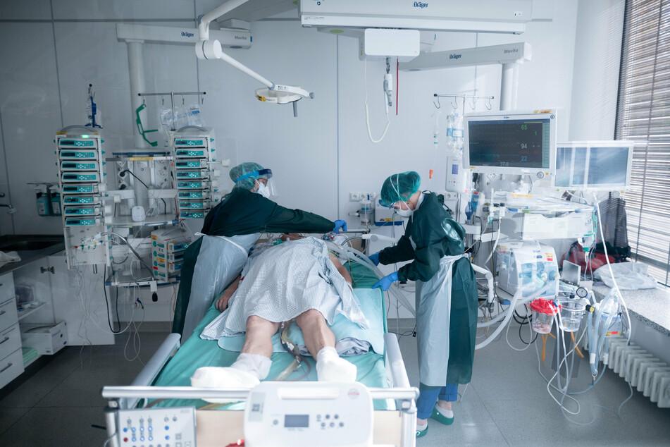 Mitarbeiterinnen der Pflege in Schutzausrüstung betreut einen Corona-Patienten.