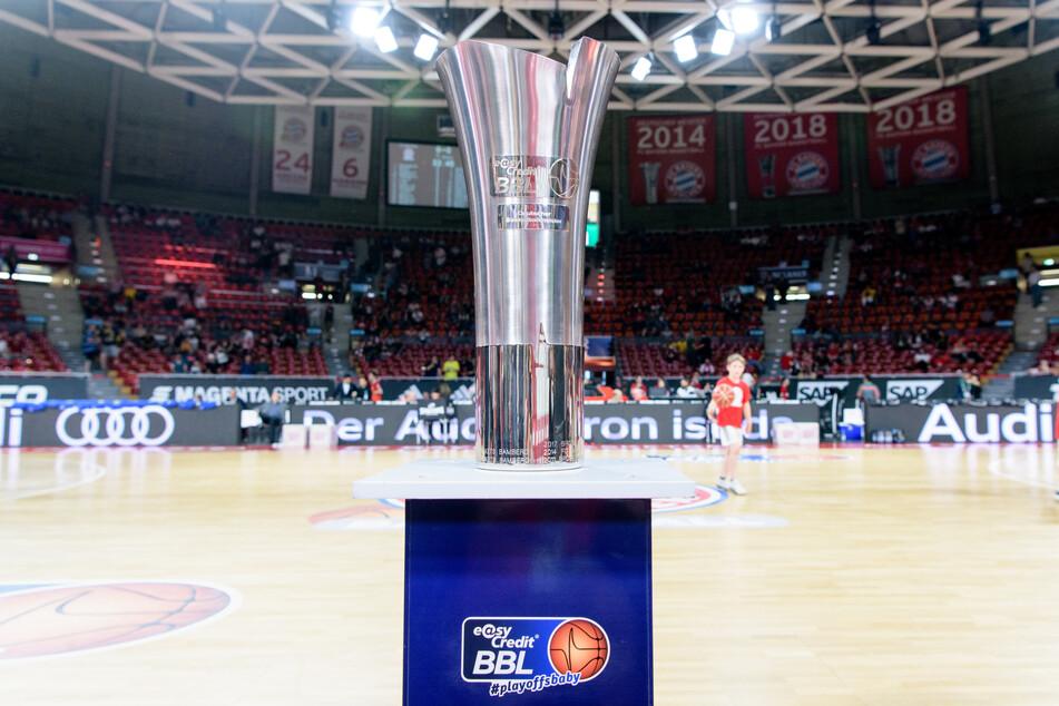 Der Ligapokal der Deutschen Basketball Bundesliga steht vor Spielbeginn auf einem Podest am Spielfeldrand. (Archivbild)