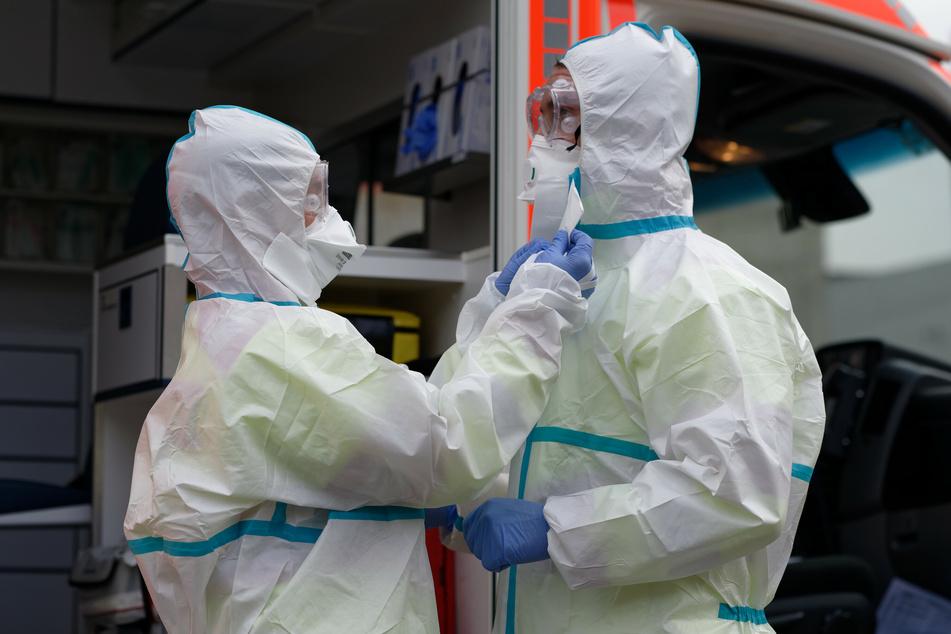 Zwei Rettungssanitäter demonstrieren bei einem Pressetermin der Feuerwehr in Köln Infektionschutzkleidung.