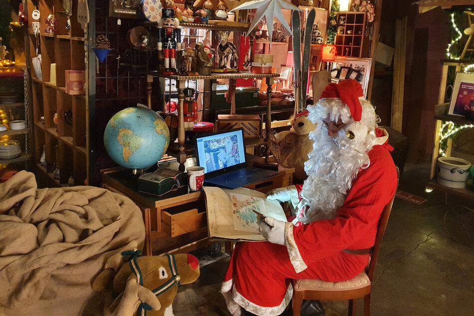 Ein Mann in einem Weihnachtsmann-Kostüm sitzt mit Smartphone und Tablet an einem kleinen Schreibtisch.