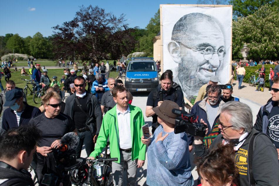 Im Hintergrund ist eine Zeichnung von Mahatma Gandhi, dem Helden der indischen Unabhängigkeitsbewegung, zu sehen.