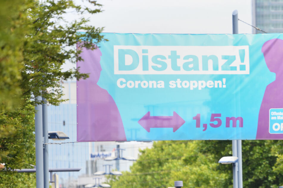"""Ein großes Plakat mit der Aufschrift """"Distanz ! Corona stoppen !"""" prangte im August 2020 am Ortseingang von Offenbach."""