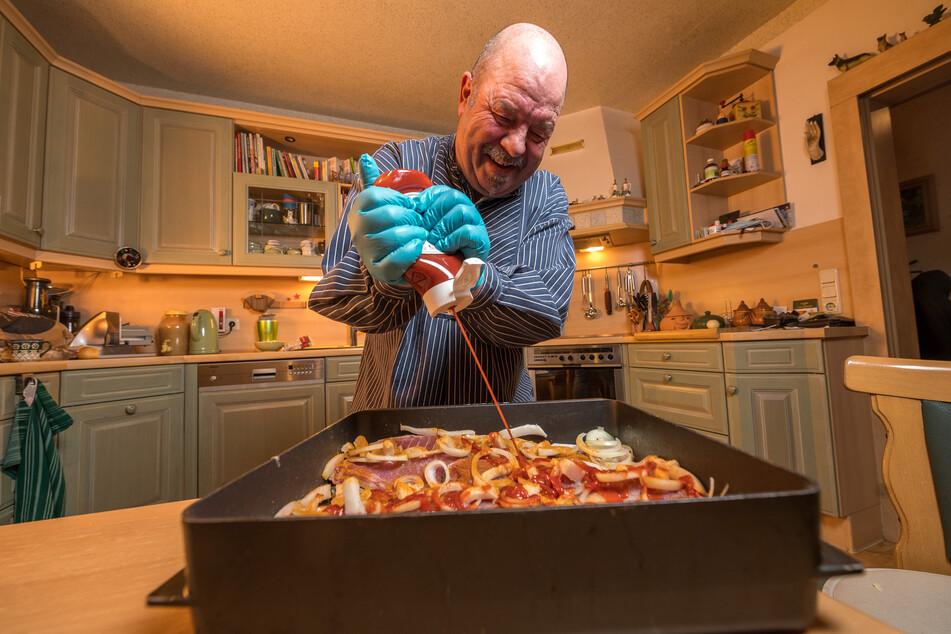 Armin Kittner macht das Kochen sichtlich Freude. Fröhlich verteilt er den Ketchup über den Fisch.
