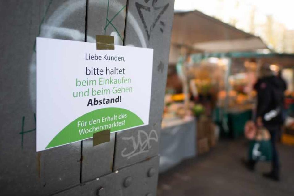"""Ein Schild mit der Aufschrift """"Liebe Kunden, bitte haltet beim Einkaufen und beim Gehen Abstand! Für den Erhalt des Wochenmarktes!"""" hängt an einem Pfeiler auf dem Isemarkt."""