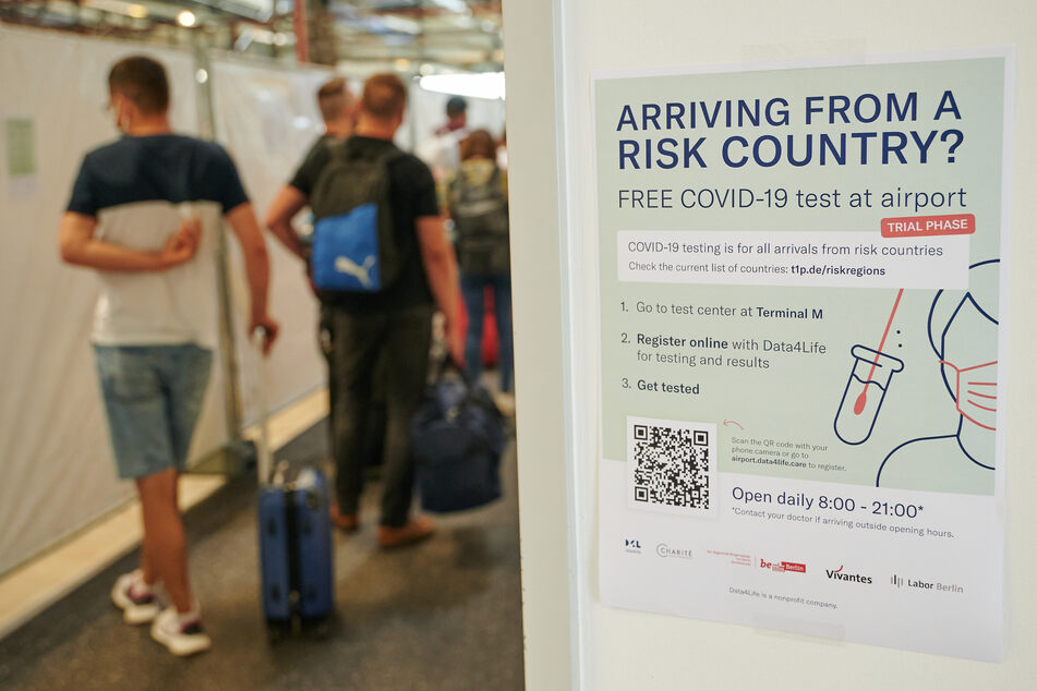 Ankommende Passagiere stehen zum kostenlosen Test im Berliner Flughafen Schönefeld an.