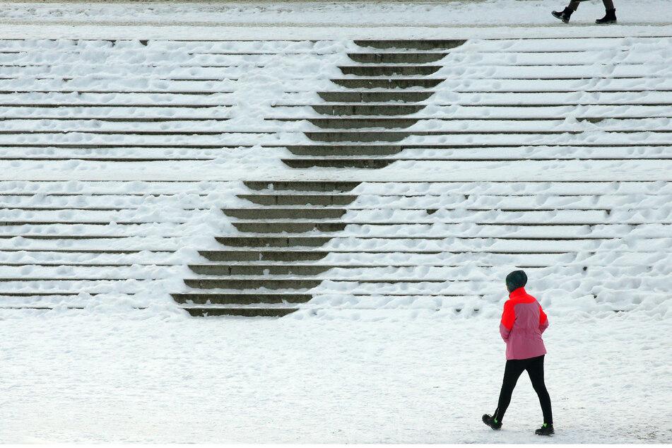 Eine Frau läuft bei Temperaturen um Minus sechs Grad Celsius im Bezirk Mitte an den verschneiten Treppen zum Reichstagsgebäude entlang.