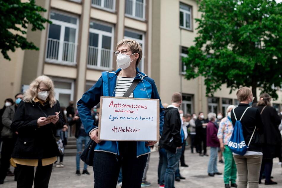 """Birgit Wehrhöfer (55) trägt ein Schild, auf dem """"Antisemitismus bekämpfen! Egal, von wem er kommt! #niewieder"""" steht."""