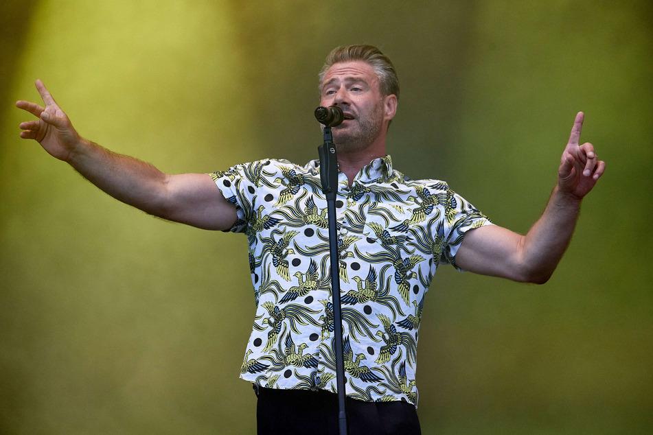 Der Sänger Sasha (49) steht auf der Bühne des Strandkorb-Open-Air-Konzerts am Cruise Center Steinwerder.