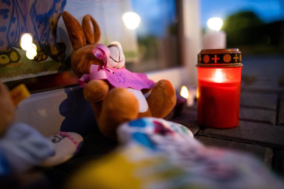 Zwei Stofftiere und Kerzen liegen vor dem Eingang einer Kindertagesstätte.