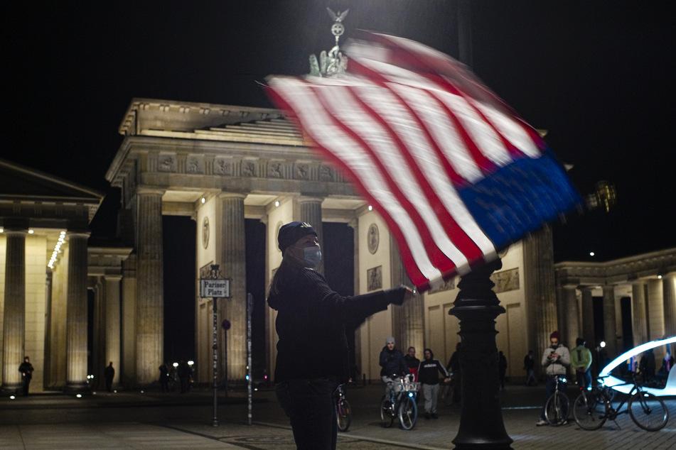 Marianne Hoenow aus Connecticut in den USA feiert den Sieg des designierten Präsidenten Joe Biden und der designierten Vizepräsidentin Kamala Harris vor dem Brandenbuger Tor in Berlin neben der Botschaft der Vereinigten Staaten.
