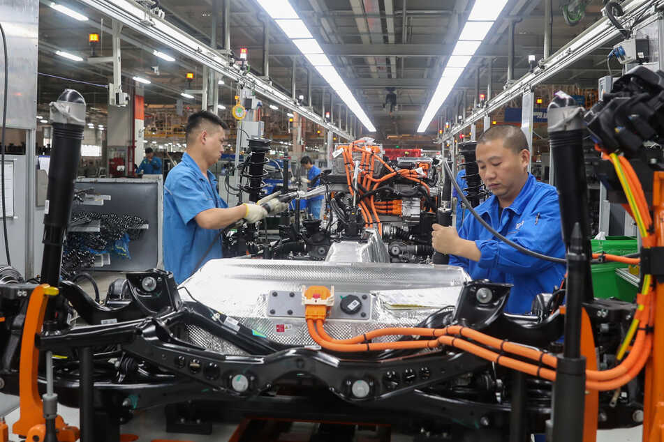 China, Shanghai: Fahrzeugbauer arbeiten in einer Werkshalle in einer Produktionslinie von SAIC Volkswagen. Die Auswirkungen der Corona-Krise ziehen sich für deutsche Unternehmen in China länger hin als erwartet.