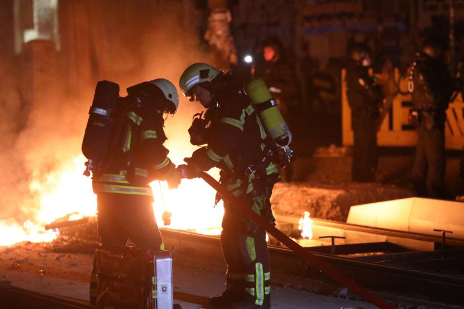 Feuerwehrleute haben sich zur brennenden Barrikade vorgekämpft und beginnen mit den Löscharbeiten.