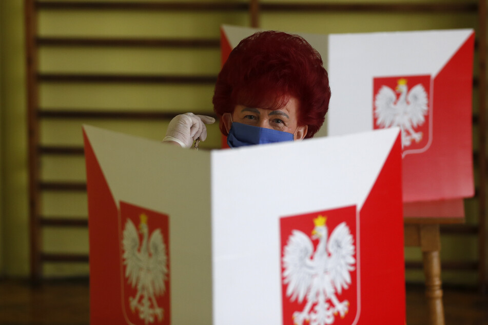 Eine Wählerin trägt in einer Wahlkabine einen Mundschutz. Um diesen abzunehmen, braucht es künftig ein ärztliches Attest.