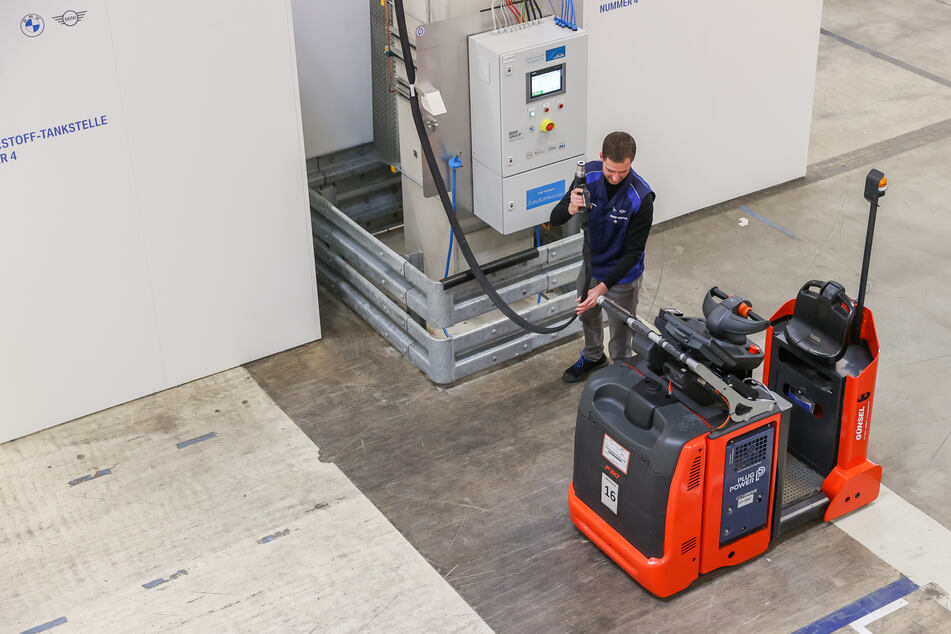 Ein BMW-Mitarbeiter betankt einen Routenzug mit Brennstoffzelle an einer Wasserstofftankstelle.