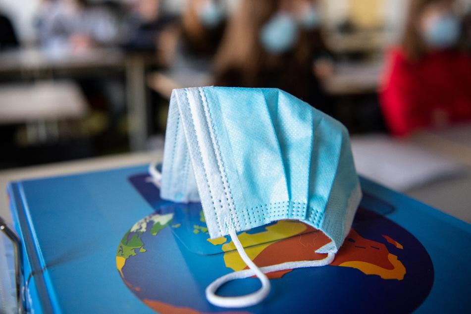 Ein medizinischer Mund- und Nasenschutz liegt während des Unterrichts an einem Gymnasium in einer Schulklasse.