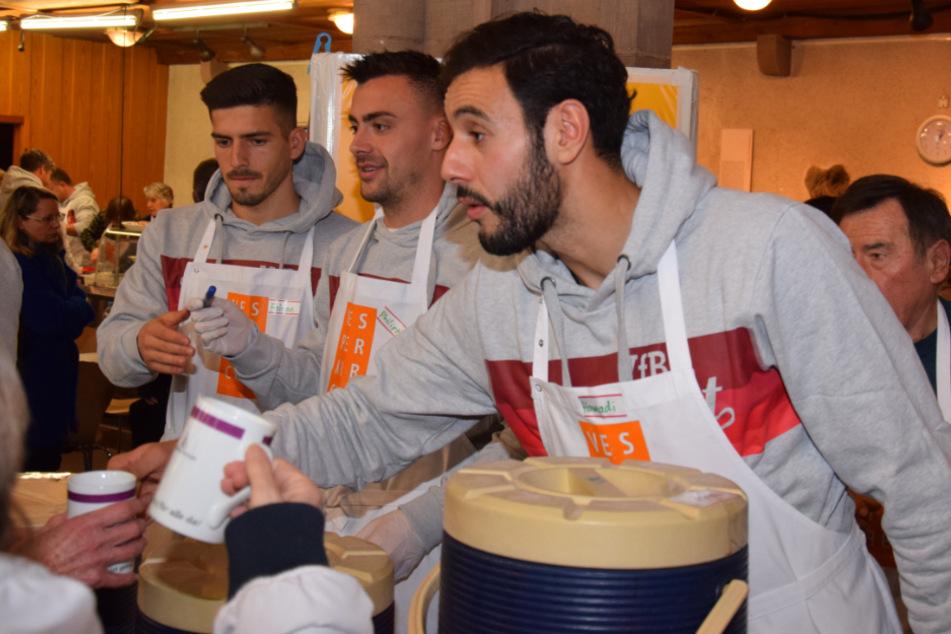Torhüter Fabian Bredlow, Mittelfeldspieler Philipp Förster und Stürmer Hamadi Al Ghaddioui (von links nach rechts) an der Getränkeausgabe.
