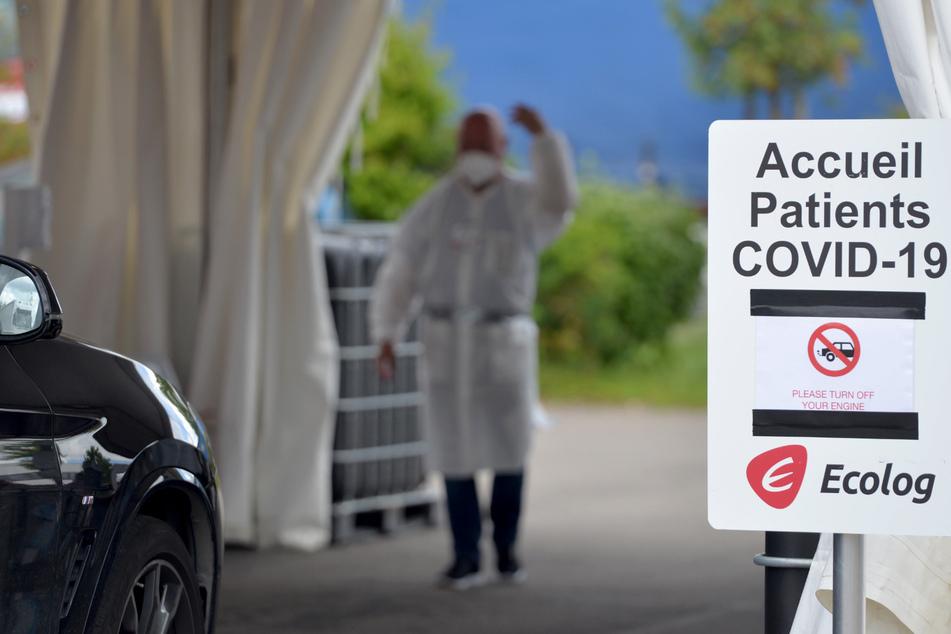 Luxemburg: Ein Medizinischer Mitarbeiter winkt einen Autofahrer in die Station, um diesen auf den Coronavirus zu testen.