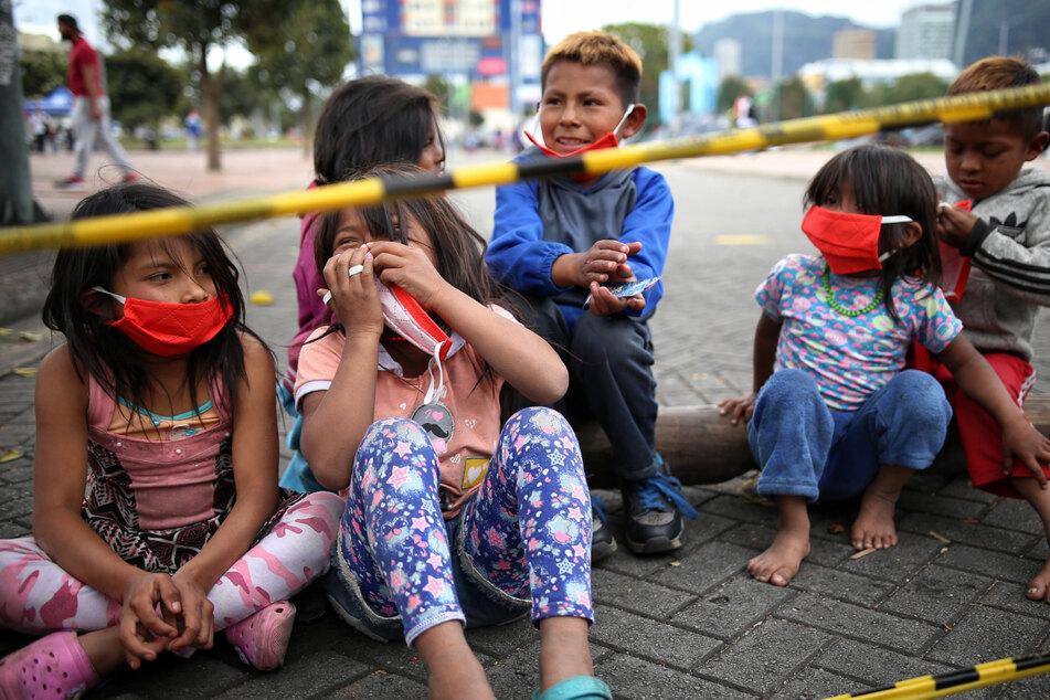 Kolumbien, Bogotá: Kinder mit Mundschutz sitzen in einem Lager der indigenen Gemeinschaft der Embera in Bogota.