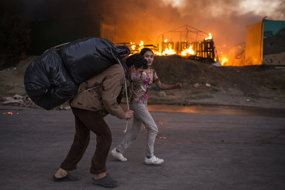 Refugees flee with their belongings from new fires in Moria camp.