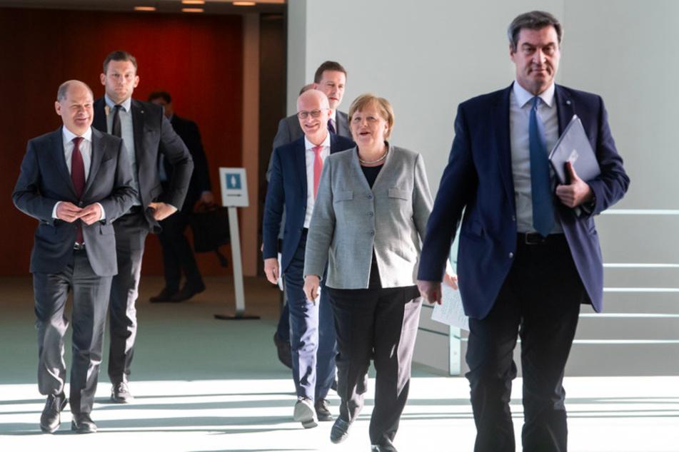 Bundeskanzlerin Angela Merkel (2.v.r., CDU) kommt zusammen mit Olaf Scholz (l, SPD), Bundesfinanzminister, Markus Söder (r, CSU), Ministerpräsident von Bayern, und Peter Tschentscher (M, SPD), Erster Bürgermeister von Hamburg zu einer Pressekonferenz im Bundeskanzleramt.