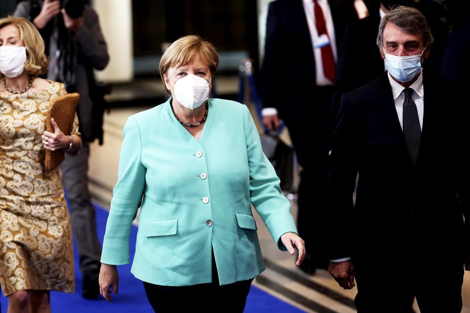 Bundeskanzlerin Angela Merkel (CDU, M) und David Sassoli (r), Präsident des Europäischen Parlaments, tragen bei ihrer Ankunft im Europäischen Parlament Mundschutze.