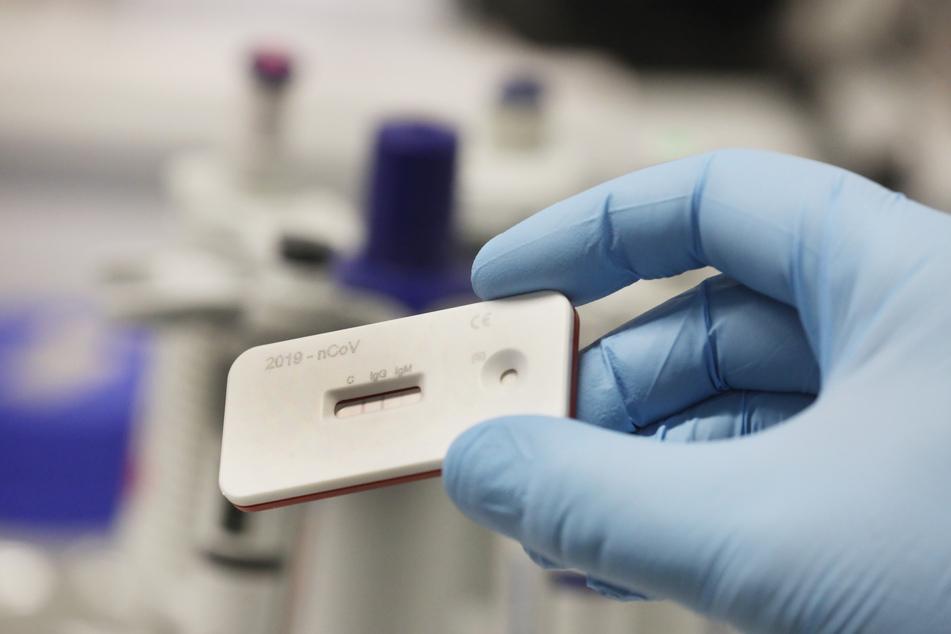 Ein Wissenschaftler zeigt einen Corona Schnelltest im Leibnitz Institut für Photonische Technologien.