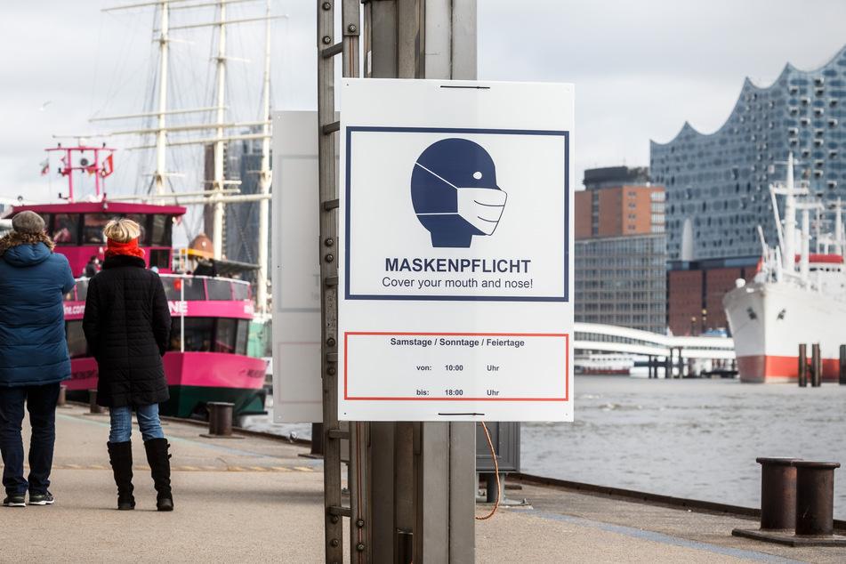 Ein Hinweisschild zur Maskenpflicht hängt auf den Landungsbrücken an der Elbe. Jogger müssen hier keine Maske mehr tragen. (Archivbild)