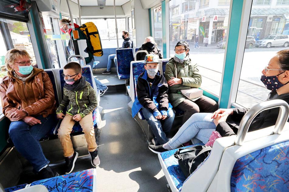 Fahrgäste sitzen mit Mund-Nasenbedeckungen in einer Straßenbahn in Rostock.