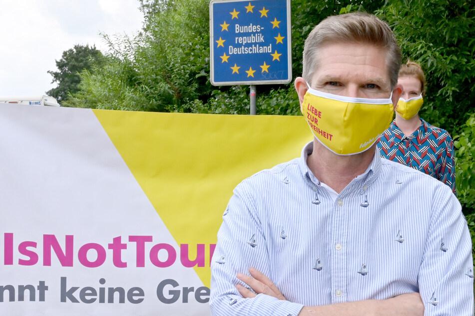Mit einer Schutzmaske steht Heiner Garg (54), FDP-Landesvorsitzender und Gesundheitsminister von Schleswig-Holstein, bei einer Demonstration am Grenzübergang Padborg.