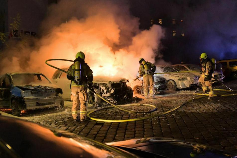 Feuerwehrleute löschen den Brand in Berlin-Mitte, bei dem insgesamt fünf Autos beschädigt oder zerstört wurden.
