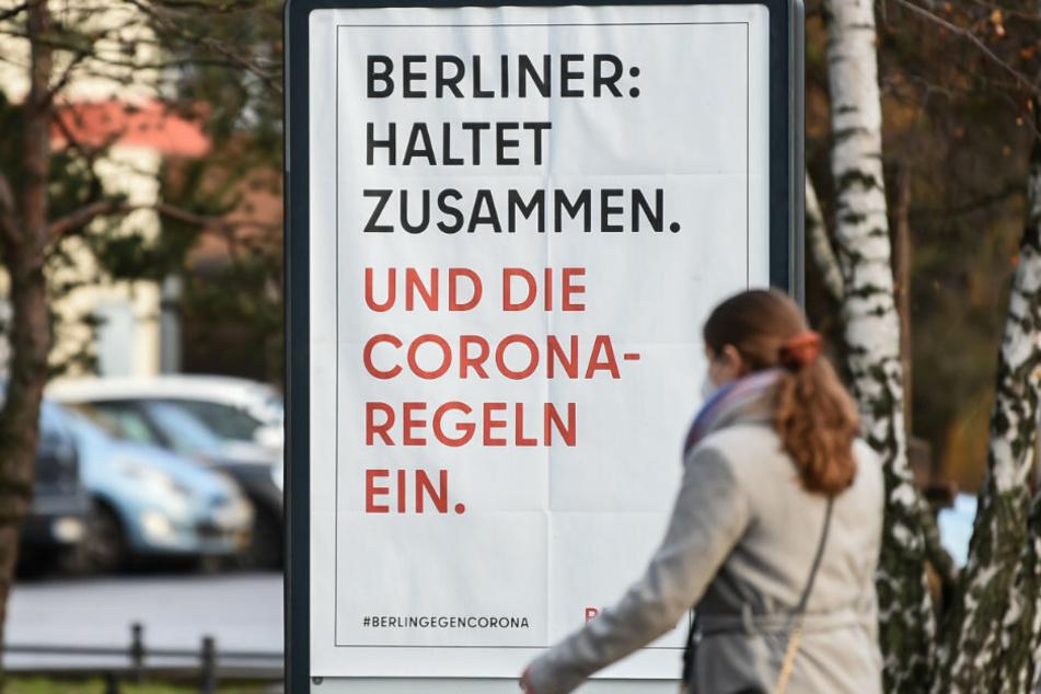 """Auf dem Gehweg steht ein Schild mit der Aufschrift """"Berliner: Haltet zusammen. Und die Corona-Regeln ein."""", während eine Frau daran vorbei geht."""