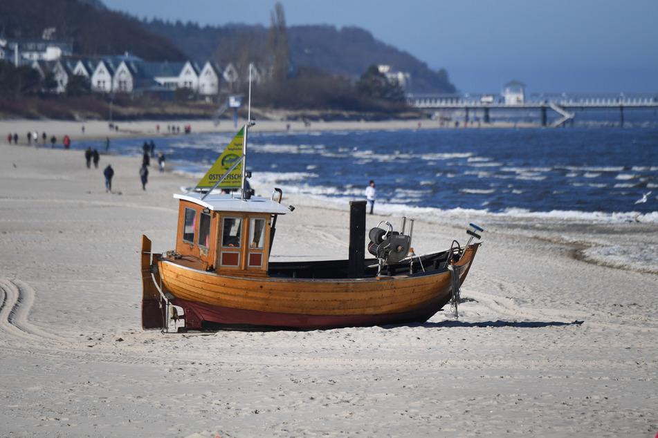 Spaziergänger sind am Strand von Ahlbeck auf der Insel Usedom unterwegs.