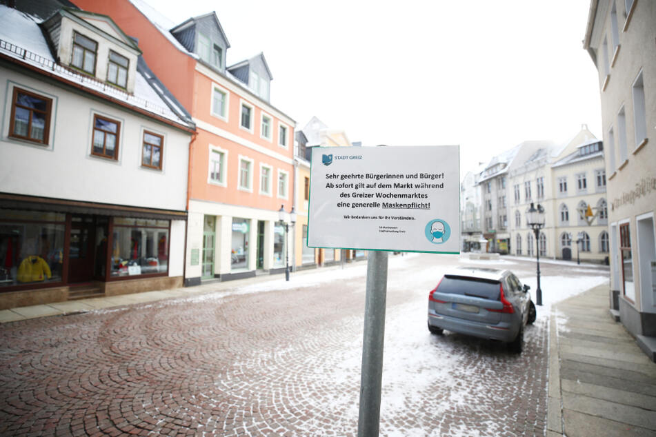 Ein Hinweisschild auf die Maskenpflicht steht am Marktplatz in der Innenstadt von Greiz. In Thüringen sind die Inzidenzzahlen im bundesweiten Vergleich weiter am höchsten.
