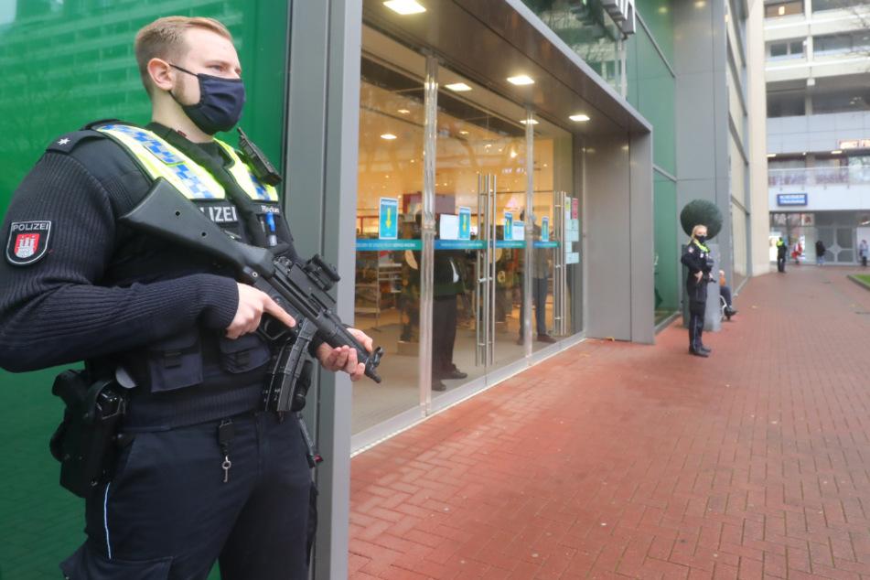 Ein mit einer Maschinenpistole bewaffneter Polizist steht vorm AEZ in Poppenbüttel.