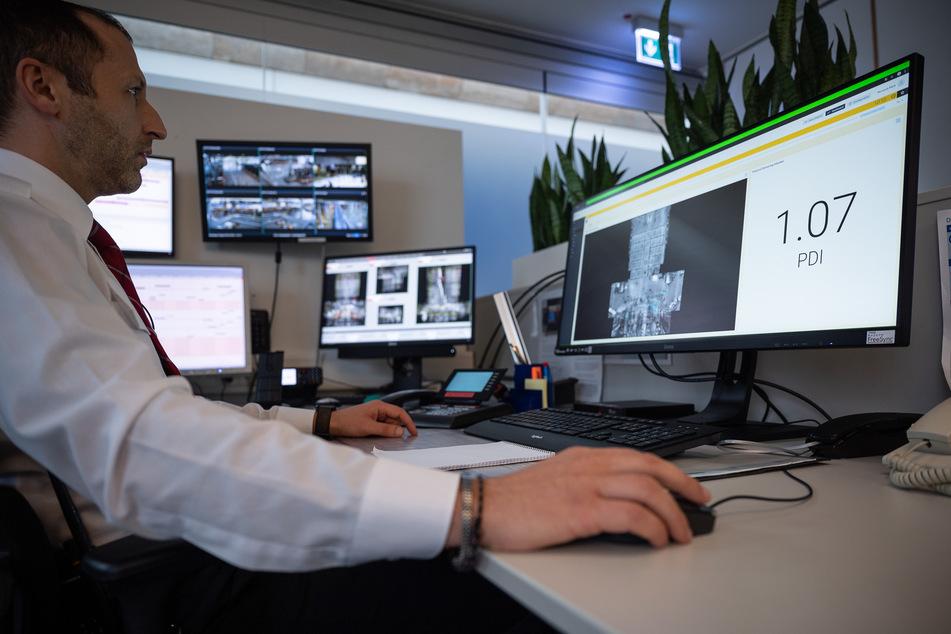 Ein Mitarbeiter sitzt am Flughafen Stuttgart in einem Kontrollraum vor einem Computer, auf dem die Ergebnisse von Überwachungssensoren anzeigt werden.