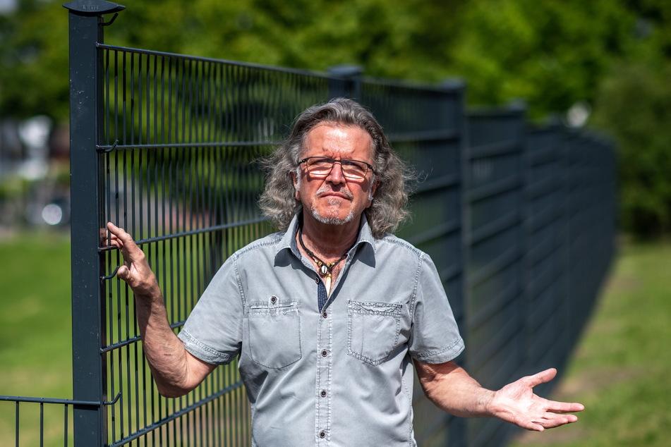 Anwohner Frank Bartzsch (66) aus Adelsberg kritisiert die weiträumige Einzäunung einer Grünanlage.