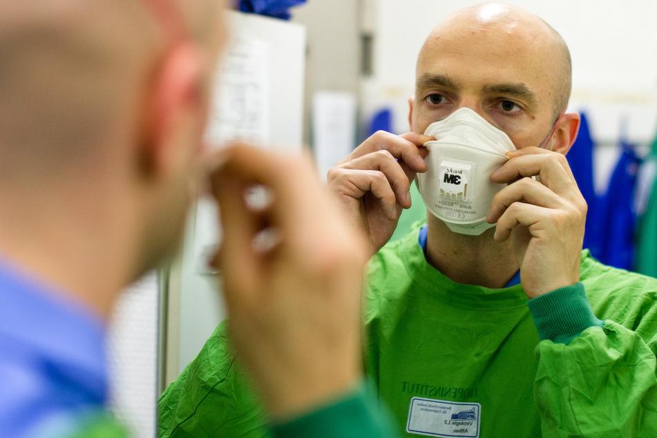 Jonas Schmidt-Chanasit, der Leiter der Virusdiagnostik des Bernhard-Nocht-Institut für Tropenmedizin, setzt sich in einer Sicherheitsschleuse vor einem Genlabor eine Atemschutzmaske auf.