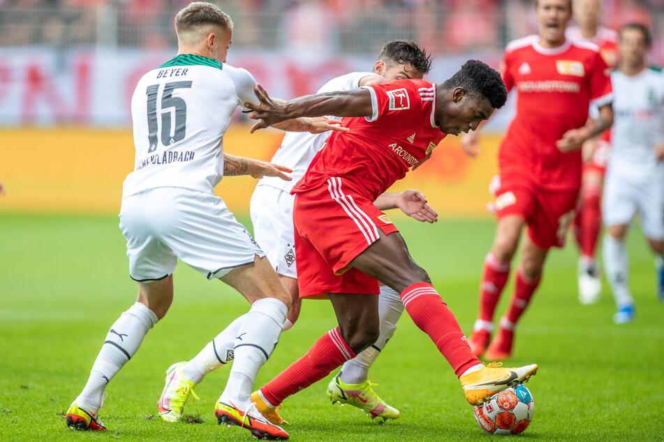 Union-Angreifer Taiwo Awoniyi (24, 3.v.l.) behauptet gegen die beiden Gladbacher Jordan Beyer (21, l.) und Joe Scally (18, verdeckt) den Ball.