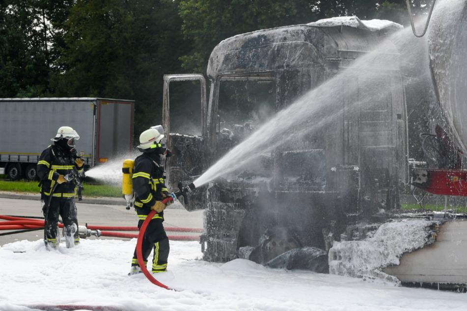 Feuerwehrleute kämpfen löschen das Fahrzeug mit Schaum.
