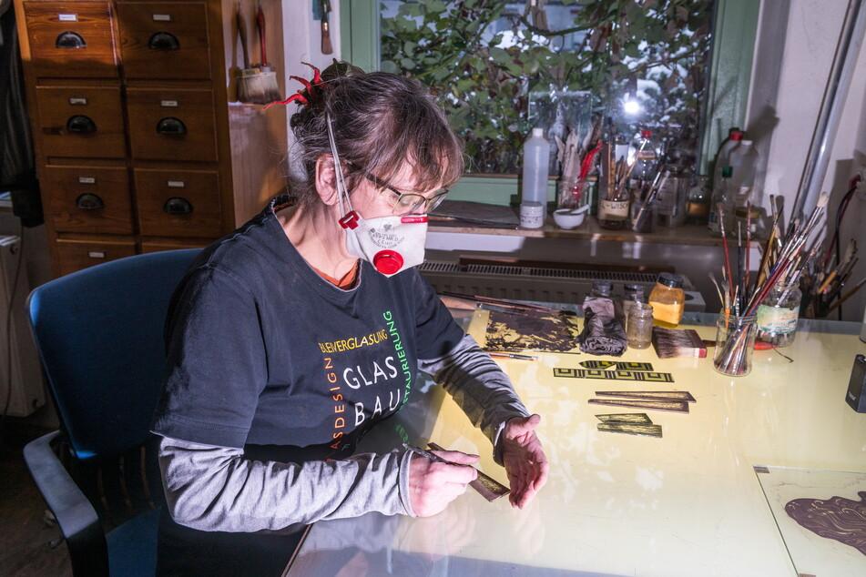 Sylvia Putzschke (58) bemalt einen Glasriegel, der neu ins Fenster eingesetzt wird.