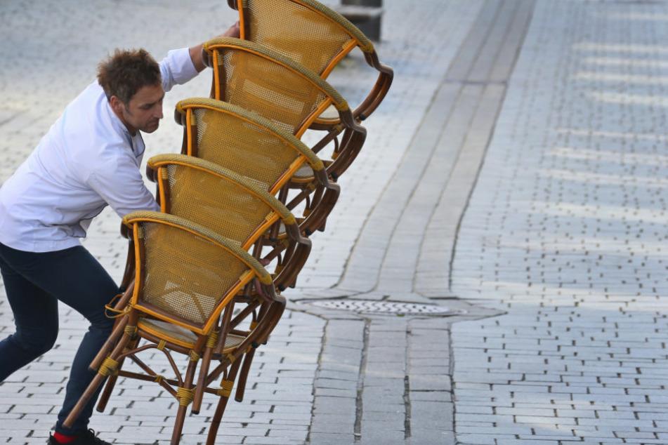 Kempten: Ein Mitarbeiter eines Straßencafes trägt gegen 15 Uhr aufeinander gestapelte Stühle in sein Lokal.