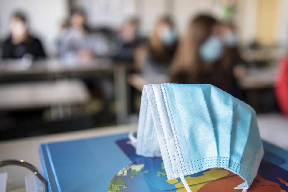 Ein Mund- und Nasenschutz liegt im Unterricht auf einem Weltatlas.