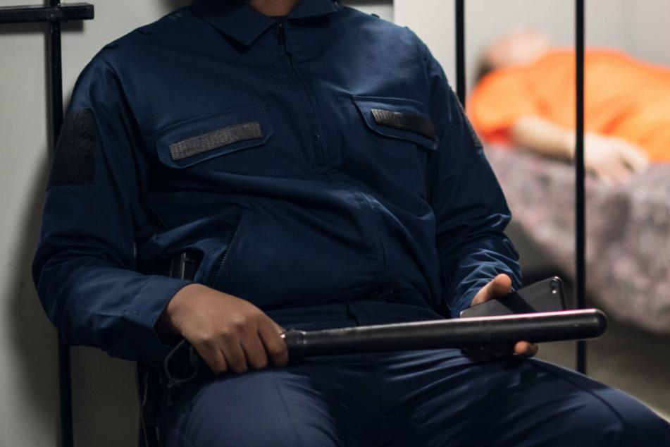 Ein Polizist bewacht einen Gefangenen in einer Haftanstalt. (Symbolbild)