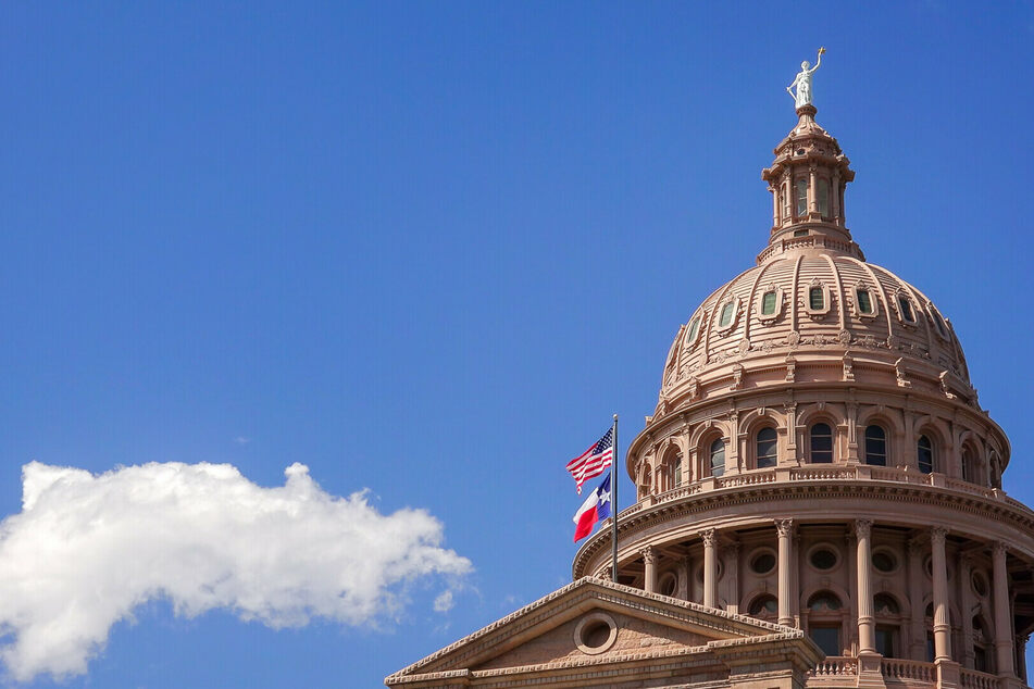 The Texan and US flags fly over the Texas State Capitol in Austin.