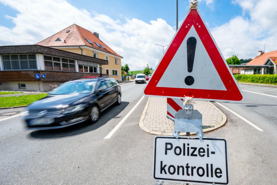 """Autos fahren an der deutsch-tschechischen Grenze hinter einem Schild mit der Aufschrift """"Polizeikontrolle"""" Richtung Tschechien."""