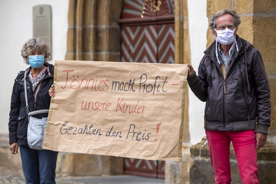 """Demonstranten halten während einer Mahnwache zur Situation beim Fleischwerk Tönnies auf dem Marktplatz in Rheda-Wiedenbrück ein Schild mit der Aufschrift """"Tönnies macht Profit - unsere Kinder bezahlen den Preis!""""."""