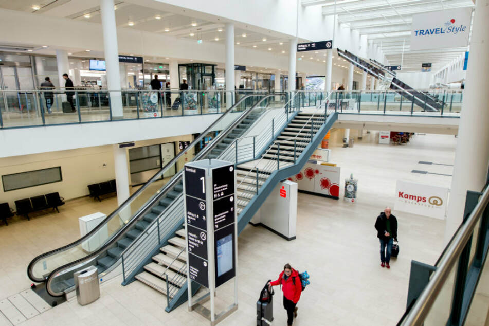 Reisende gehen mit ihrem Gepäck durch das Terminal am Flughafen Bremen.