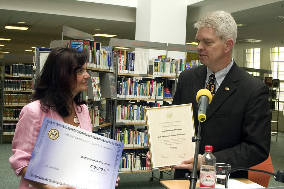 """Spende für Bibliothekschefin Elke Beer: US-Generalkonsul Mark D. Scheland eröffnete in Chemnitz die Aktion """"America @ your library""""."""