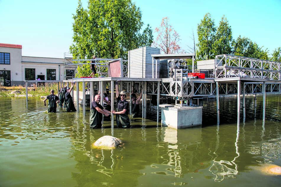 Ein elfköpfiges Team ist nötig, damit die Bühne im Wasser aufgebaut werden kann. Gut 300 Bodenplatten mussten sie verlegen.