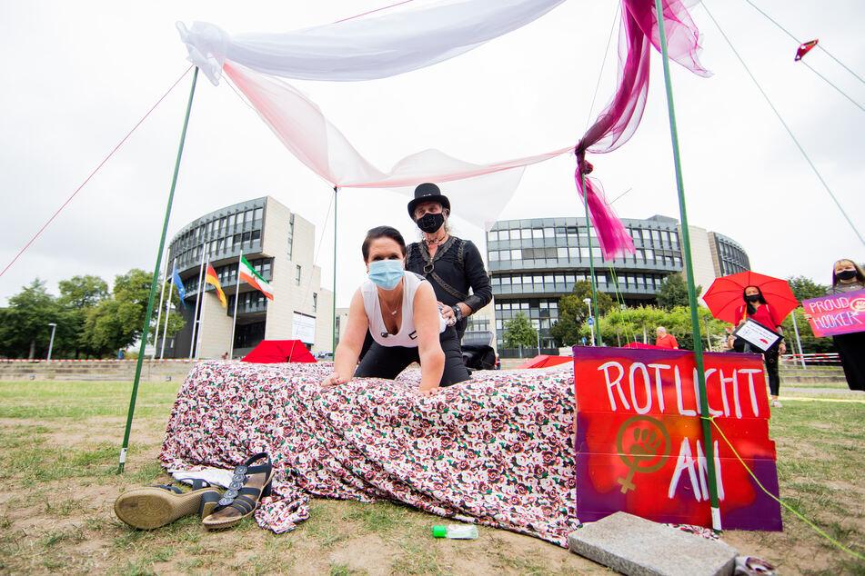 Thomas und Nicole, Straßen-Sexarbeiterin, demonstrieren auf einem Bett vor dem Landtag, wie bezahlte Sexangebote während der Corona Pandemie aussehen könnten.